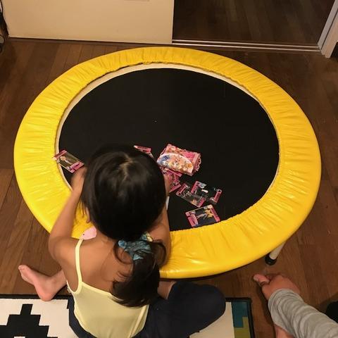 トランポリンをテーブルのようにして遊ぶ子ども